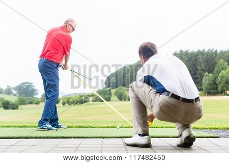 Golf trainer working with golf player on driving range