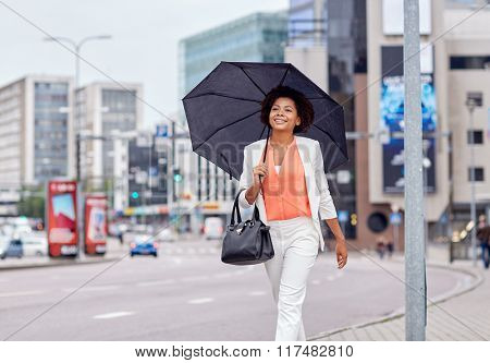 business and people concept - young smiling african american businesswoman with umbrella and handbag walking down city street