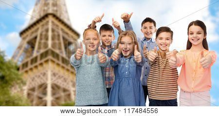 childhood, travel, tourism, gesture and people concept - happy smiling children showing thumbs up over paris eiffel tower background