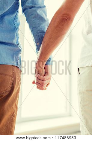 people, homosexuality, same-sex marriage, gay and love concept - close up of happy male gay couple holding hands from back