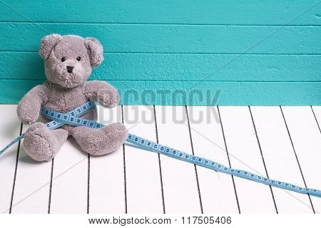 Teddy bear on a white wooden floor  blue-green background with centimeter. Diet and weight loss in c