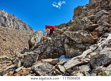 Hiking. Woman with a backpack gently descends on large boulders . Mountains of Eastern Siberia poster