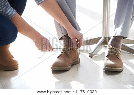 Adult Daughter Helping Senior Tie Shoelaces
