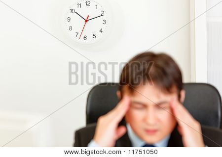 Stressed businessman aware of approaching deadline. Focus on clock