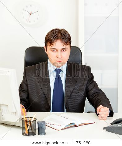 Dissatisfied modern businessman banging fist on table