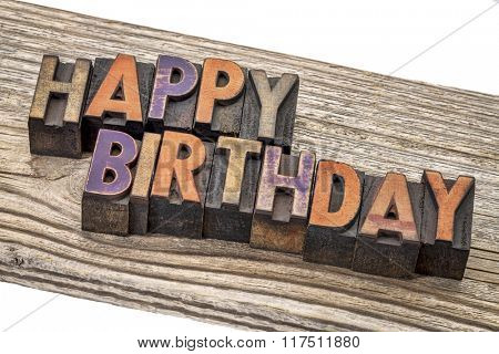happy birthday greeting card - text  in vintage letterpress wood type printing blocks against a grained cedar plank
