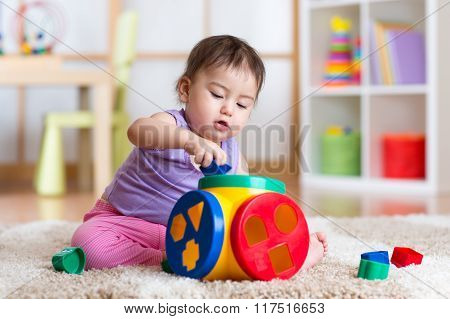 kid girl plays with educational toy indoor