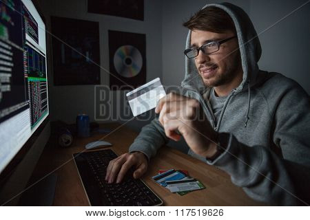 Smiling young rubber in sweatshirt with hood making purchases in internet and paying with stolen credit card