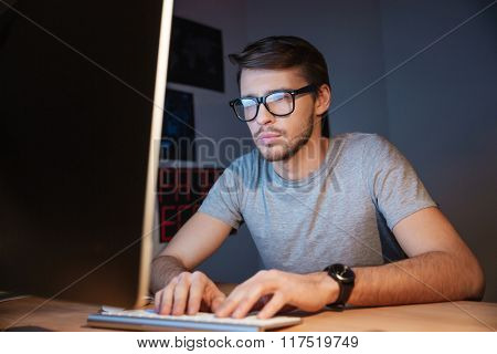 Concentrated serious young man in glasses using computer in the dark room at home
