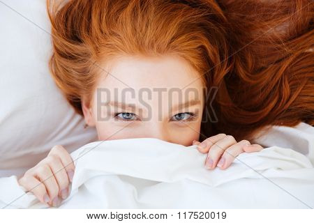 Closeup of cute lovely young woman with red hair lying and hiding under white blanket