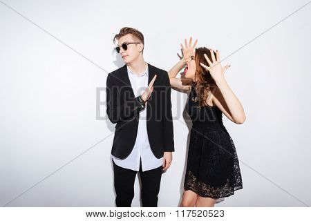 Woman in night dress shouting on man isolated on a white background