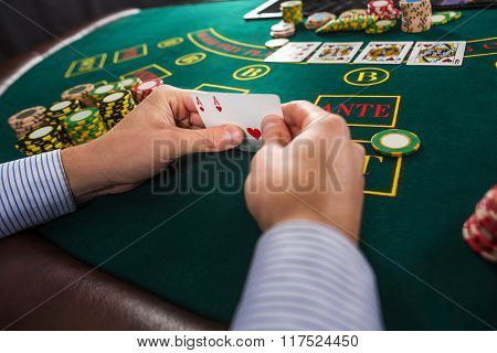 Male poker player holding the of two cards aces