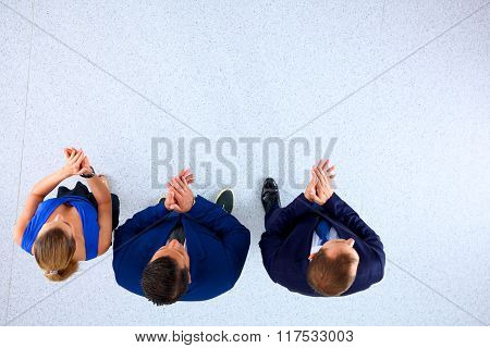 Business people standing together and clapping - topview