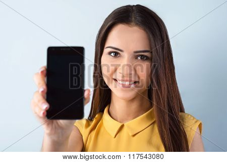 Photo of beautiful young business woman standing near gray background. Woman with yellow shirt looking at camera, smiling and showing mobile phone