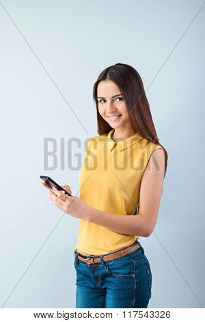 Photo of beautiful young business woman standing near gray background. Woman with yellow shirt using mobile phone, smiling and looking at camera