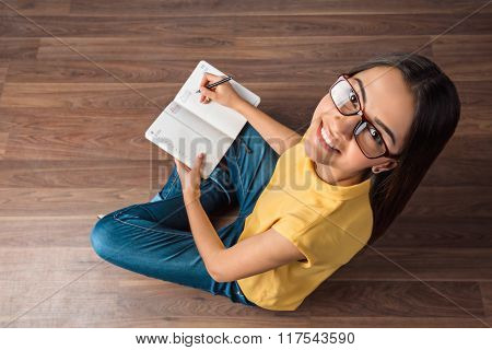 Top view photo of young business woman sitting on wooden floor. Woman with glasses holding notebook, smiling and looking at camera