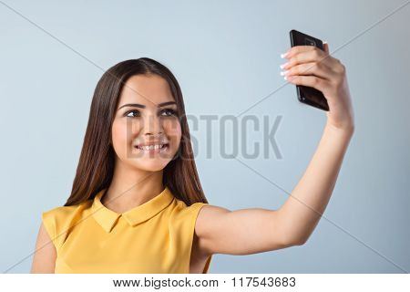 Photo of beautiful young business woman standing near gray background. Woman with yellow shirt making selfie with mobile phone and smiling