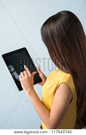 Photo of beautiful young business woman standing near gray background. Woman with yellow shirt using tablet computer