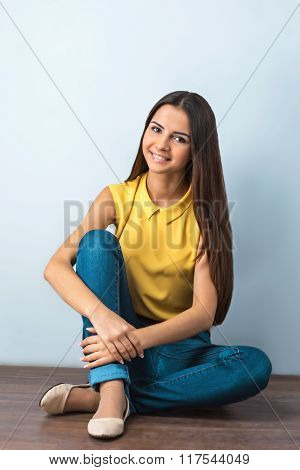 Photo of beautiful young business woman sitting on wooden floor. Smiling woman looking at camera