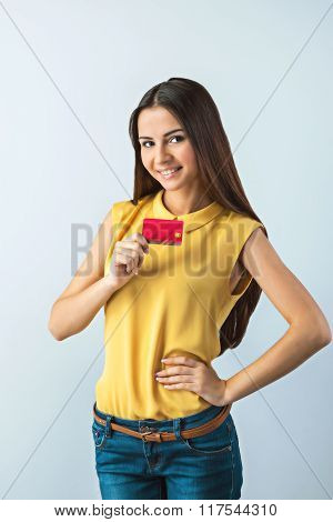 Photo of beautiful young business woman standing near gray background. Woman with yellow shirt looking at camera, smiling and showing credit card