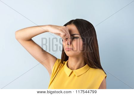 Photo of beautiful young business woman standing near gray background. Woman with yellow shirt covering her nose from smell