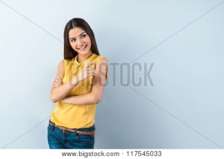 Photo of beautiful young business woman standing near gray background. Smiling woman with yellow shirt looking and pointing aside
