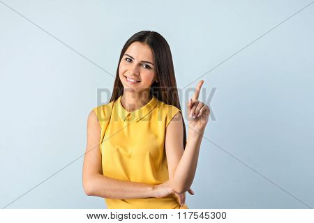 Photo of beautiful young business woman standing near gray background. Smiling woman with yellow shirt looking at camera and pointing up