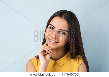 Photo of beautiful young business woman standing near gray background. Woman with yellow shirt looking at camera and smiling