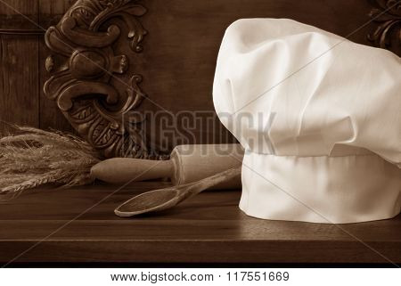 Sepia toned still-life of chef's hat in rustic setting with vintage wooden spoon and rolling pin on wood cutting board.. Decorative, carved serving tray as background. Baking or Cooking concept.s