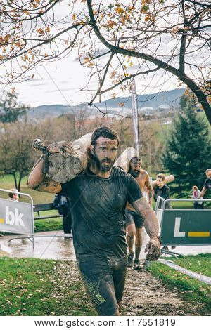 Runner carrying wooden logs in a test of extreme obstacle race