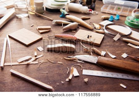Wood working. Wood carving. Making handcrafted fishing lures form balsa wood.Hand made fishing lures on a work table with tools in background. Shallow depth of field.retro muted color.