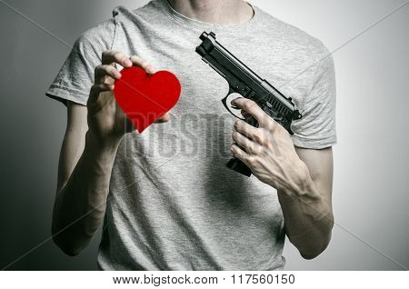 Horror and firearms topic: suicide with a gun in his hand and a red heart on a gray background poster