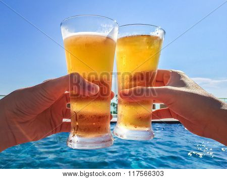 Hands Clinking Glasses Of Beer By The Pool