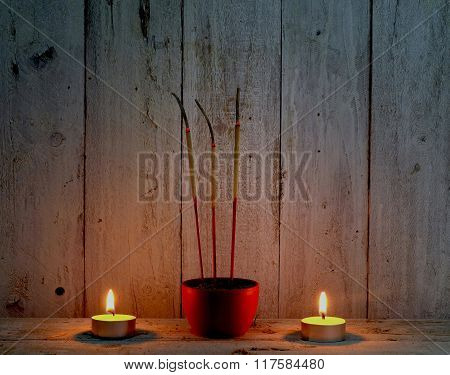 incense sticks with candle flame on wooden backgroundpray in thai traditional