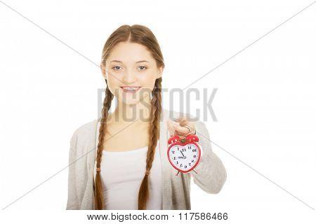 Happy teenage woman with alarmclock.