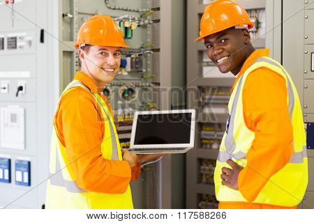 happy electrical co-workers using laptop computer checking transformer control box