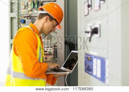 experienced electrician working in power plant control room
