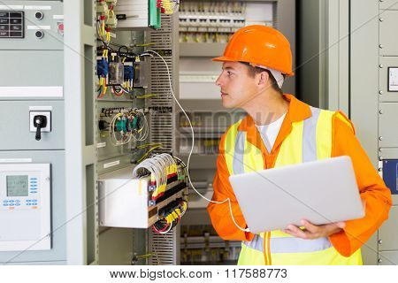 technician checking computerized transformer status with laptop computer poster