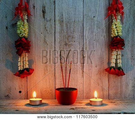 background of worship place in thai cultureburning incense sticks with the wreath of flowercandle flame
