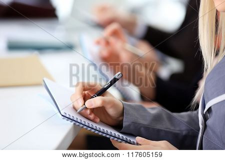 Young blonde business woman making notes at the office meeting