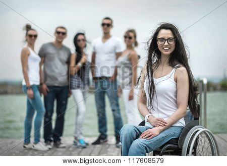Young people on the pier with them disabled friend.
