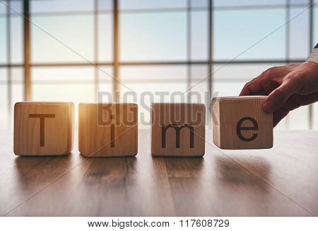 the concept of time. hand men in business suit holding the cubes which the written word time.