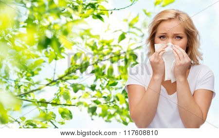 people, healthcare, rhinitis, cold and allergy concept - unhappy woman with paper napkin blowing nose over natural background poster