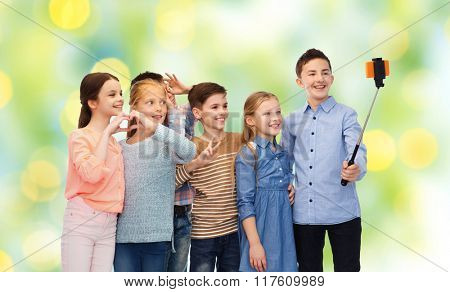 childhood, friendship, technology and people concept - happy children talking picture by smartphone on selfie stick over green lights background