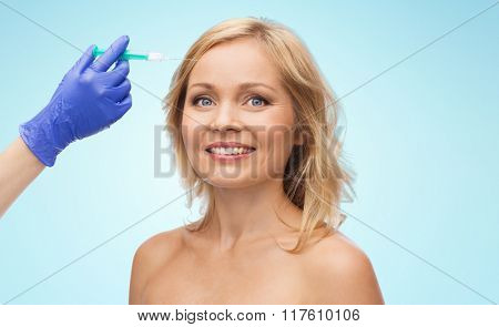 beauty, anti-aging cosmetic surgery concept - smiling woman face and beautician hand in glove with syringe making injection to forehead over blue background