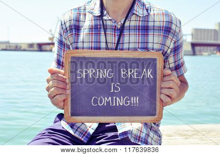 a young caucasian man sitting in a wooden pier shows a chalkboard with the text spring break is coming written in it, with a filter effect