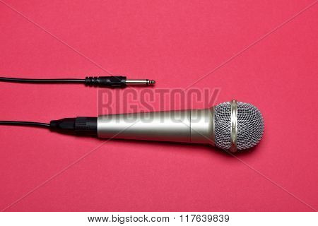 high-angle shot of a wired microphone on a red background