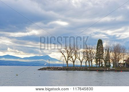Lausanne quay of Geneva Lake with trees in winter Ouchy in Switzerland. Lausanne is a city in Switzerland. Ouchy is a port and popular lakeside resort in Lausanne.