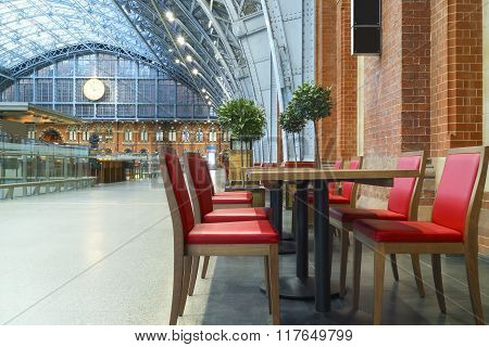 Red café chairs and tables at London international train station on upper floor