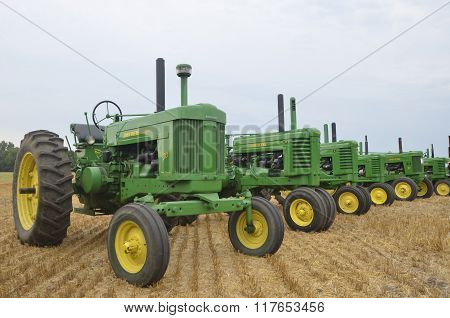 Row of two cylinder John Deere tractors